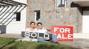 couple sitting in front of house with For Sale sign holding a Sold sign