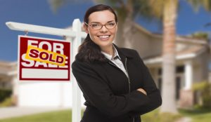 Woman agent in front of house with For Sale/Sold sign
